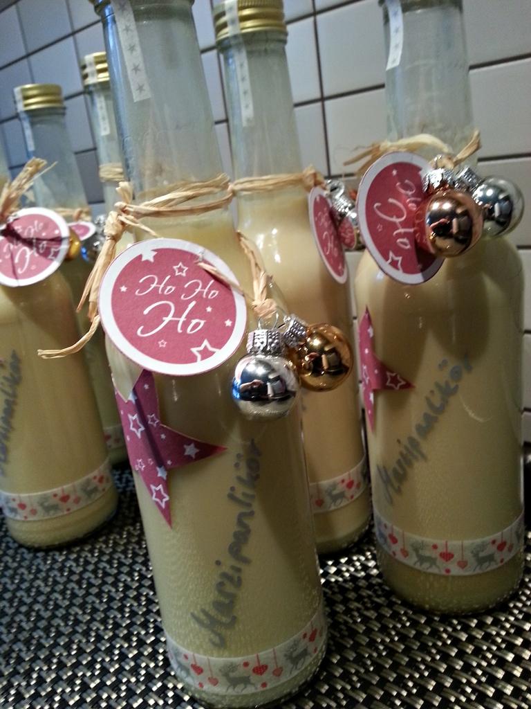 Likörflaschen weihnachtlich geschmückt.